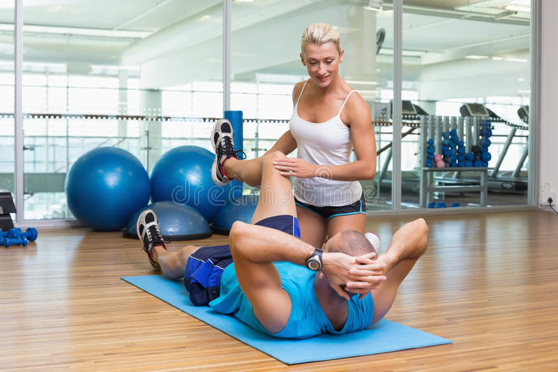 Trainer assisting man with exercises at fitness studio stock photo
