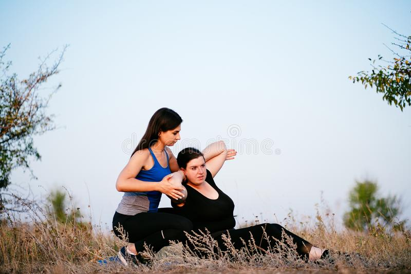 Trainer assisting overweight woman doing sit-ups. Personal trainer assisting overweight women doing sit-ups. Fitness, sport, weight loss, training, teamwork and stock photos