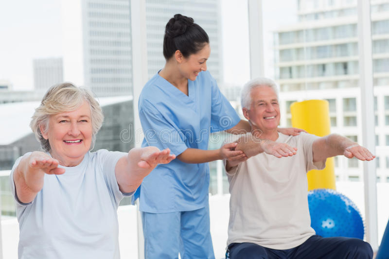 Trainer assisting senior couple in exercising stock photo