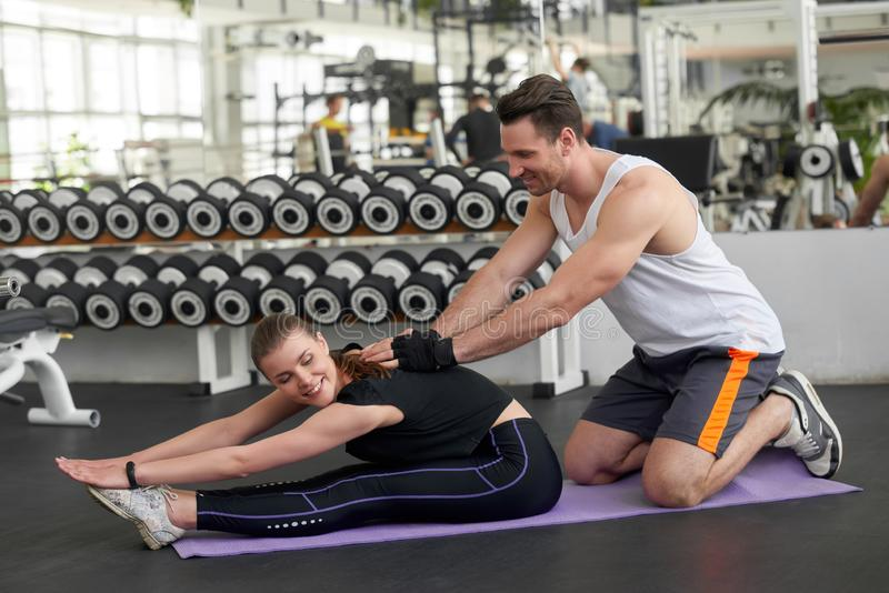 Trainer assisting woman on body stretching. stock images