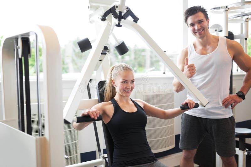 Trainer-Assisting Woman Doing-Kasten-Presse-Übung lizenzfreie stockbilder