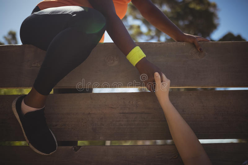 Trainer assisting woman in wooden wall climbing during obstacle course royalty free stock images