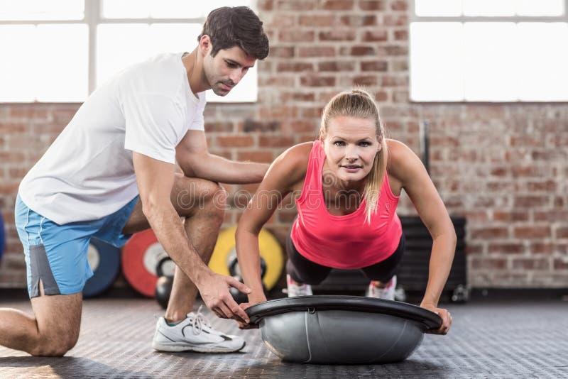 Trainer bijwonende vrouw met duw UPS bij gymnastiek royalty-vrije stock foto