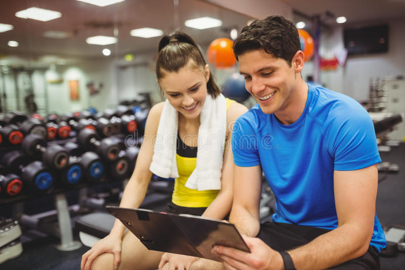 Trainer and client discussing her progress. At the gym royalty free stock photo