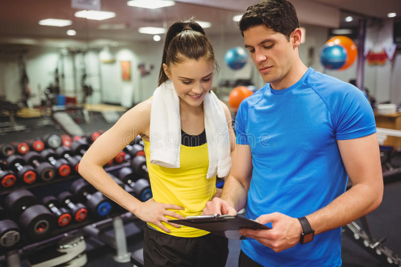 Trainer and client discussing her progress. At the gym stock photo