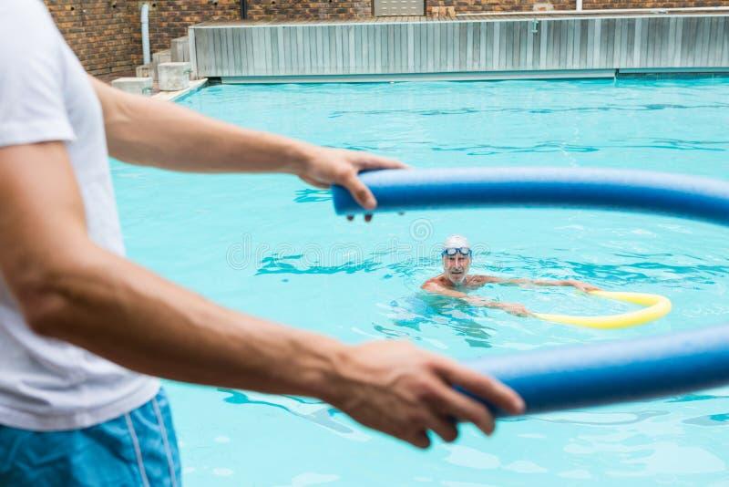 Trainer, der Gebrauch der Poolnudel demonstriert stockbild