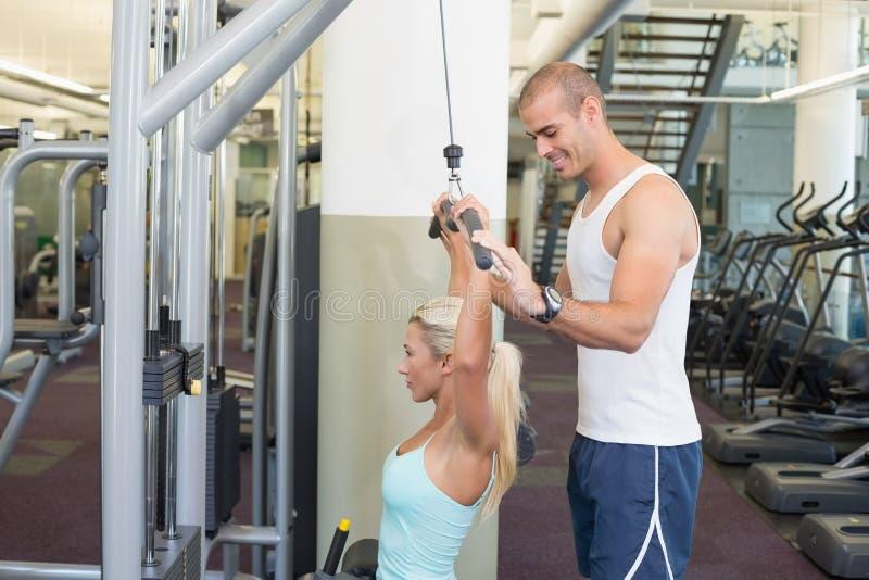 Trainer, der junge Frau auf einer Latmaschine in der Turnhalle unterstützt lizenzfreie stockfotografie