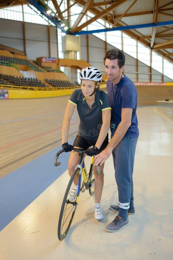 Trainer, der weg vom weiblichen Radfahrer drückt stockfotos