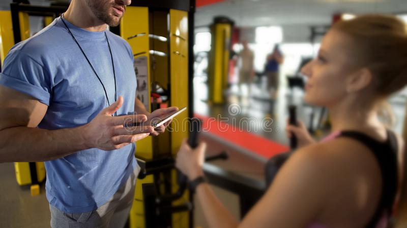 Trainer discussing training plan with his female client, coach support in gym royalty free stock image
