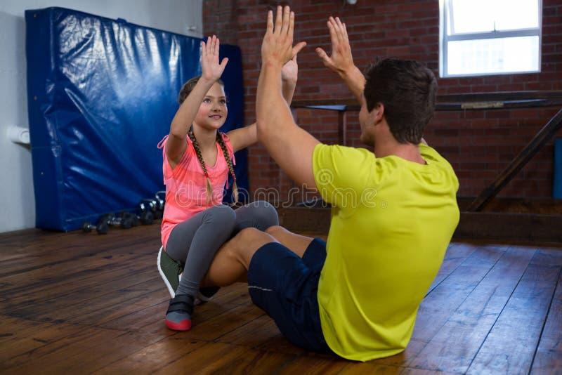 Trainer en tiener die hoogte vijf geven aan elkaar terwijl het uitoefenen royalty-vrije stock foto's