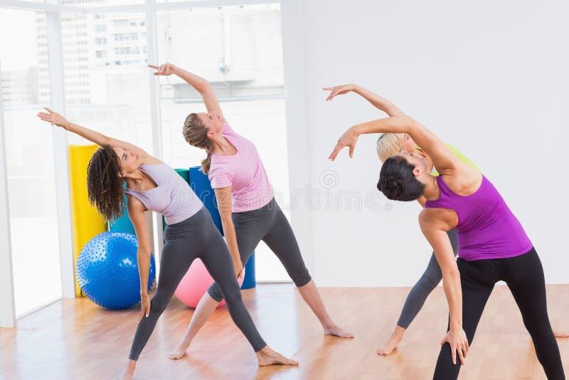 Trainer en vrouwelijke vrienden die uitrekkende oefening doen stock fotografie