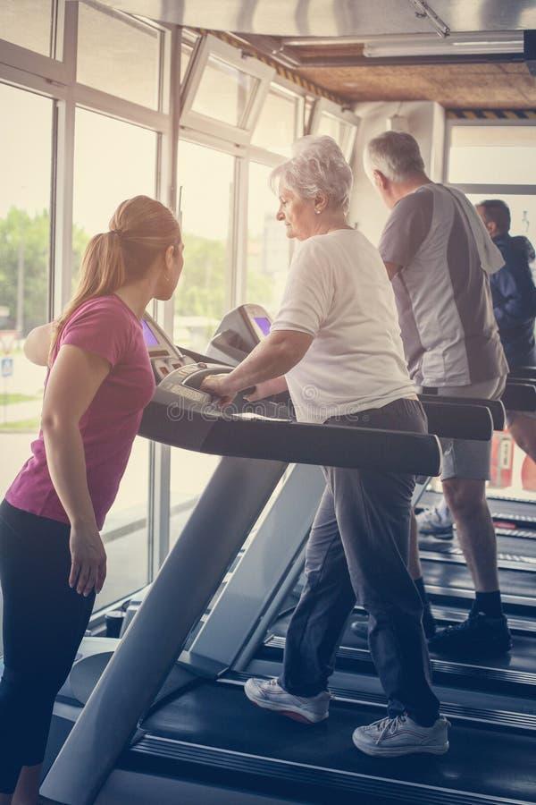 Trainer exercise helps elderly couple. Senior couple on stock photos