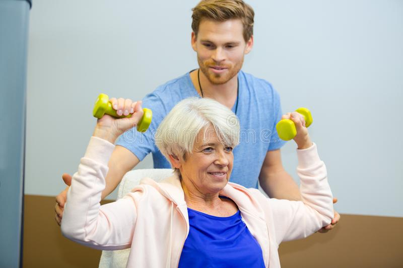 Trainer helping senior woman lift dumbbells in fitness studio royalty free stock photos