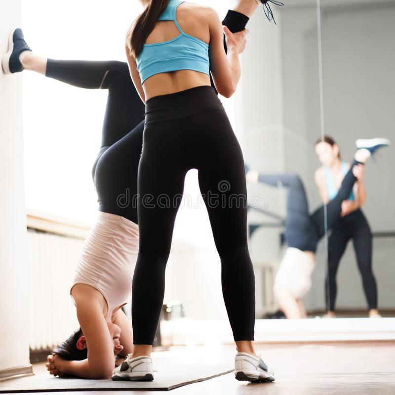 Trainer helping sporty woman to do handstand royalty free stock photo