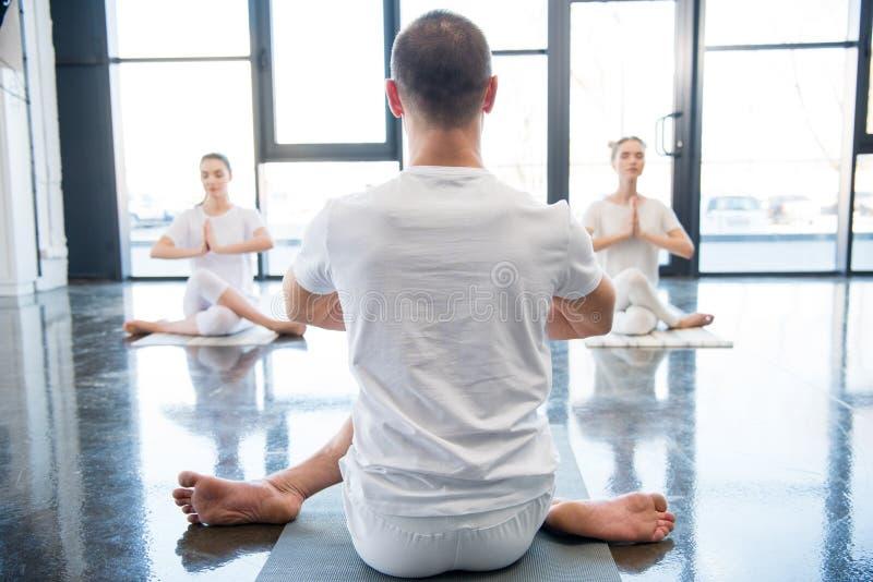 Trainer helping women practicing Gomukhasana or cow face yoga pose royalty free stock photos