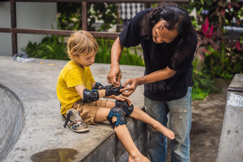 Trainer helps the boy to wear knee pads and armbands before training skate board royalty free stock photo