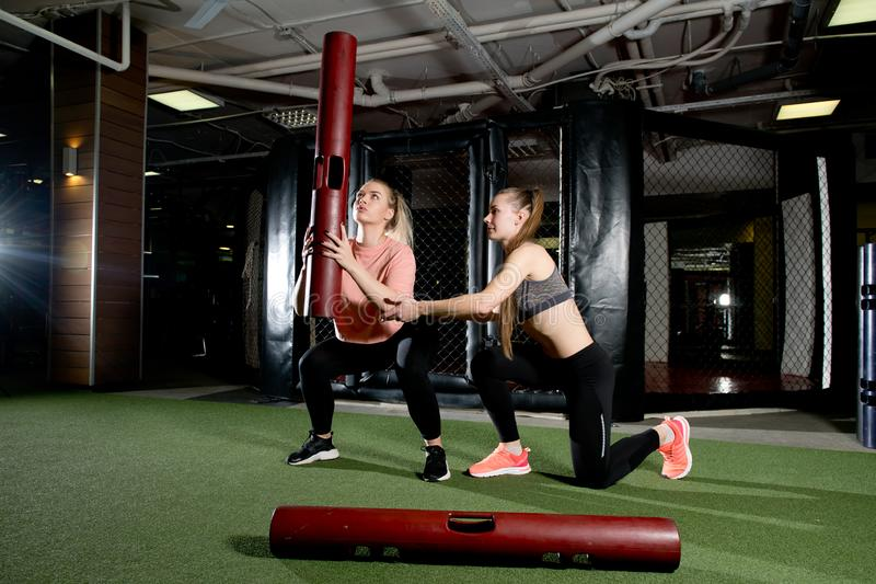 Trainer helps client keep balance using sports equipment royalty free stock photo