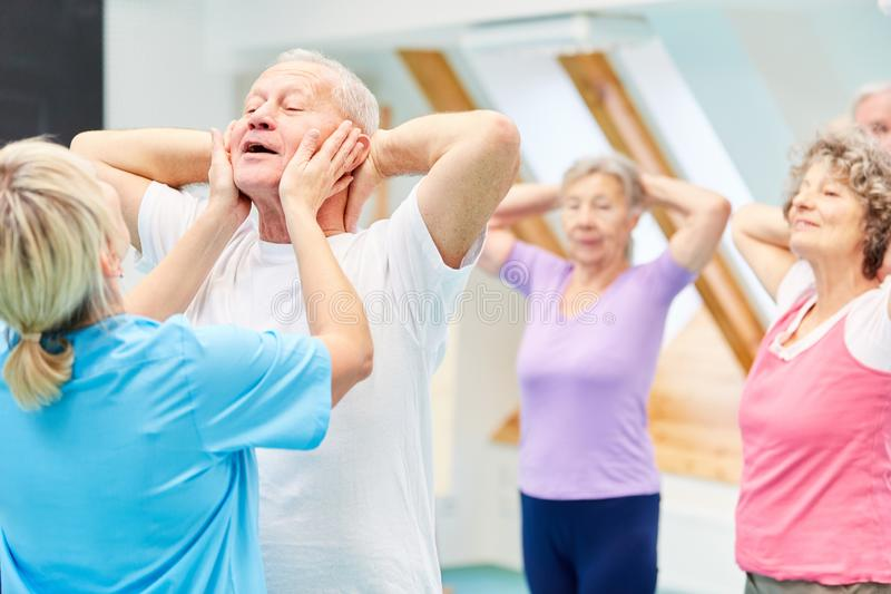Trainer helps seniors with a rehab exercise royalty free stock photo