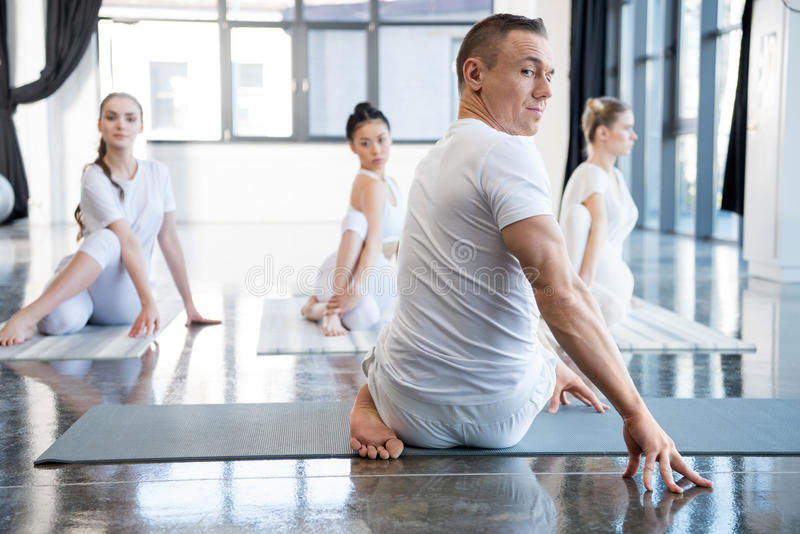 Trainer and his group practicing half spinal twist pose in gym stock image