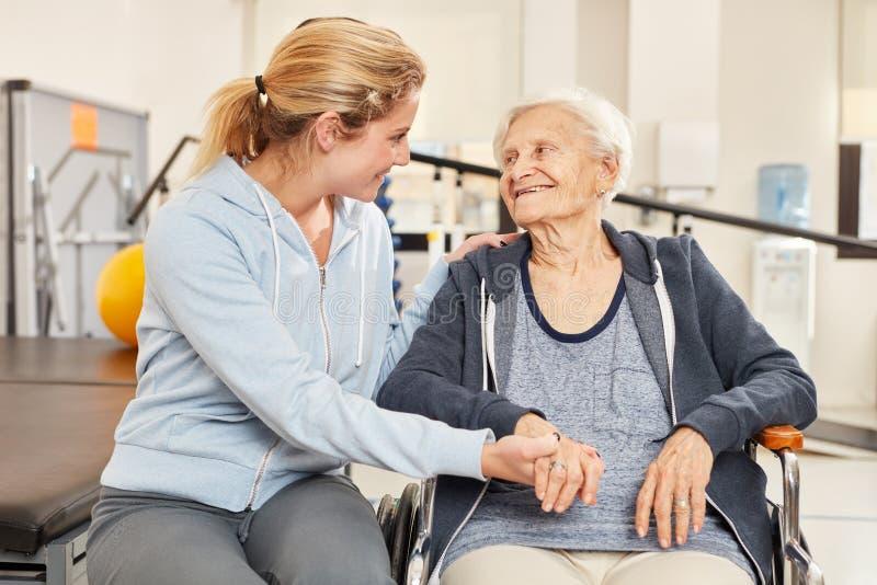 Trainer kümmert sich eine um ältere Frau in einem Rollstuhl lizenzfreies stockbild