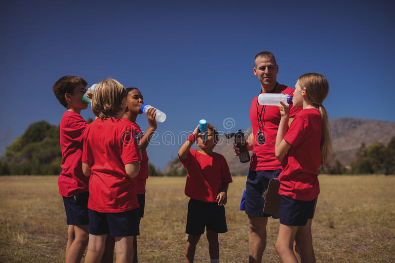 Trainer and kids drinking water in the boot camp. On a sunny day stock photography