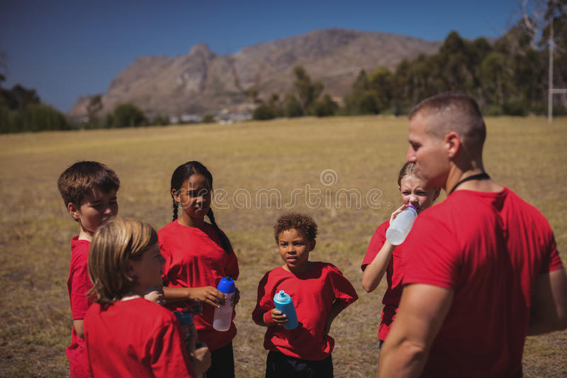 Trainer and kids drinking water in the boot camp. On a sunny day royalty free stock photography