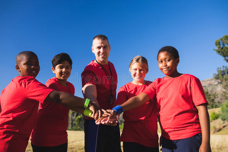Trainer and kids forming hand stack in the boot camp. On a sunny day stock photos