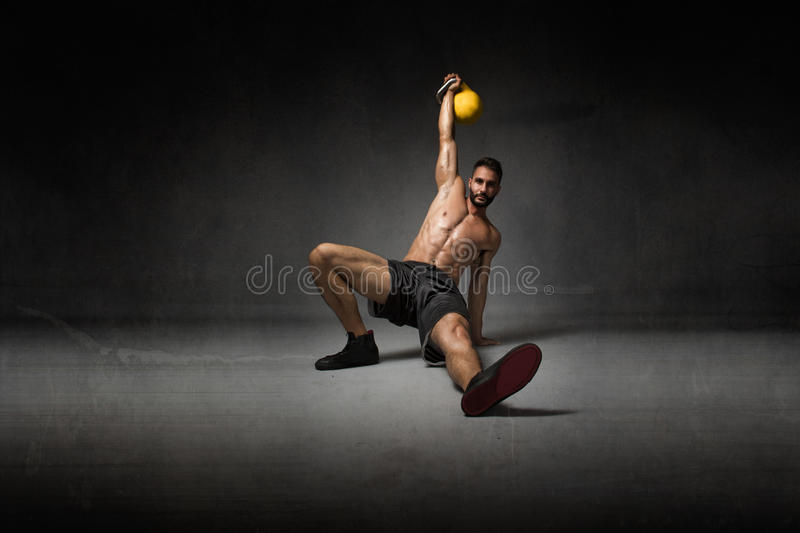 Trainer lying down with kettlebell on hand royalty free stock photography