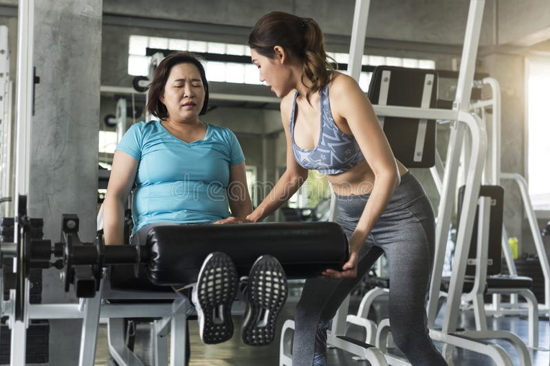 Trainer met het Aziatische hogere vrouw opheffen barbell in gymnastiek Gezond levensstijl en trainingconcept stock afbeelding