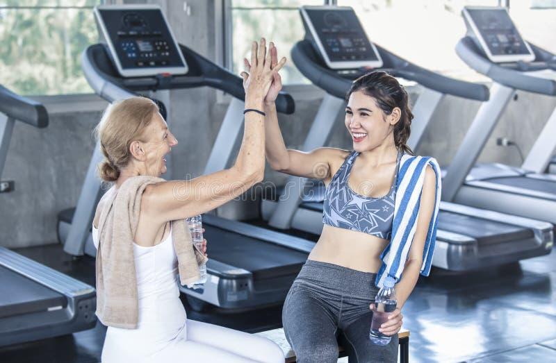 Trainer met het hogere vrouw geven highfive in geschiktheidsgymnastiek bejaard gezond levensstijlconcept royalty-vrije stock foto's