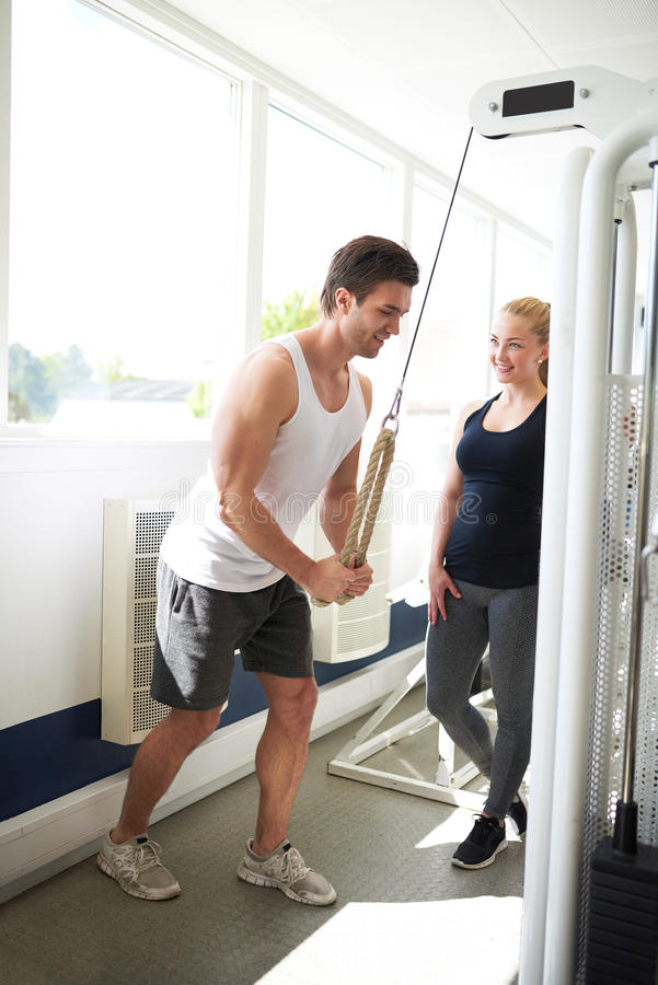 Trainer Showing how to Pull Down a Pulley to Woman royalty free stock photography
