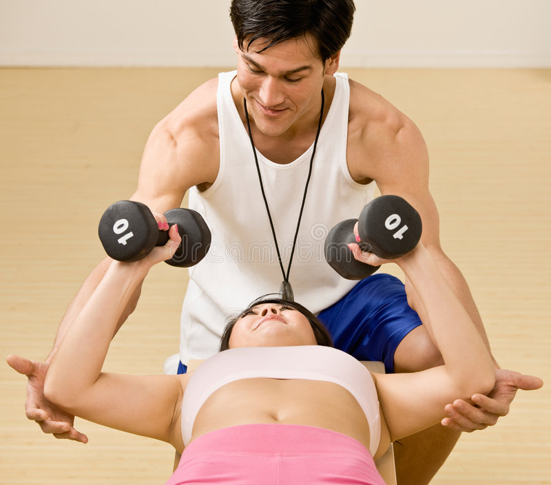 Trainer spotting woman working out stock photos