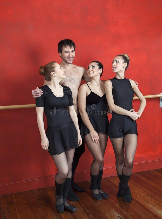 Trainer-Standing Arms Around-Ballett-Tänzer stockfotos