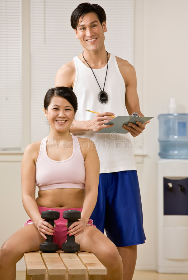 Trainer standing with woman holding dumbbells royalty free stock photos