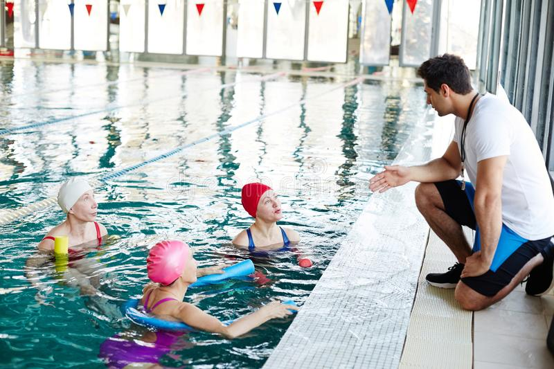 Trainer and swimmers royalty free stock photo