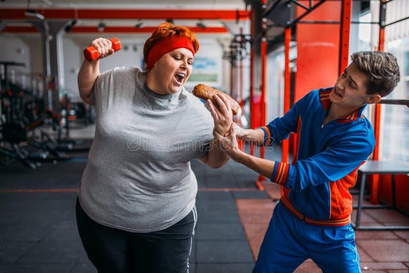 Trainer takes hotdog at fat woman, motivation stock photos