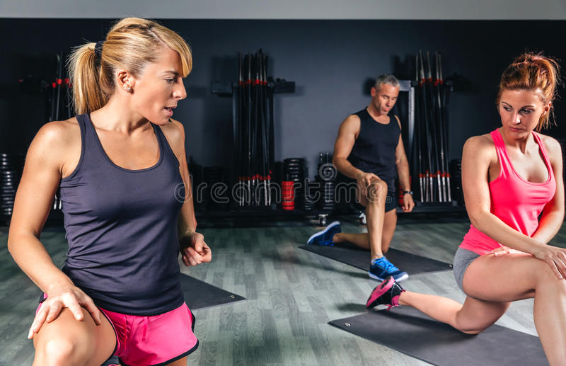 Trainer teaching stretch exercises to fitness class stock photos