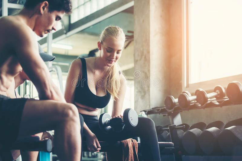 Trainer training exercise with man and woman at the gym for healthy care and body slim.  Fitness instructor exercising with his cl stock photography