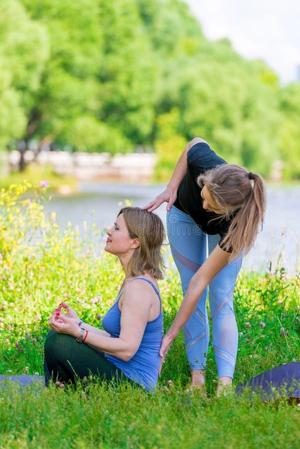 Trainer und Frau an der Yogaklasse im Lotussitz auf der Natur lizenzfreie stockfotografie