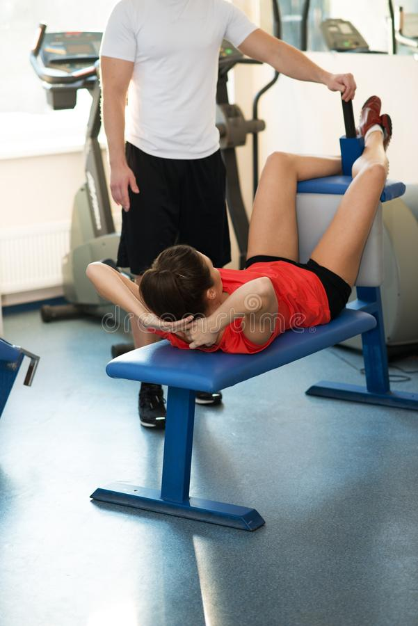 Trainer und Frau im Fitness-Club lizenzfreie stockbilder