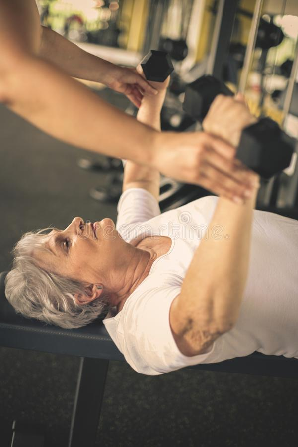 Trainer working exercise with senior woman in the gym. stock images