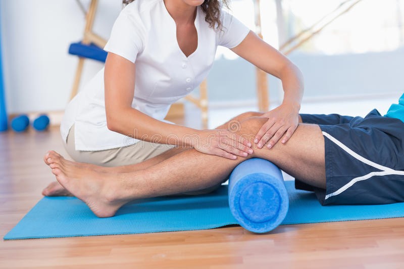 Trainer working with man on exercise mat royalty free stock photography
