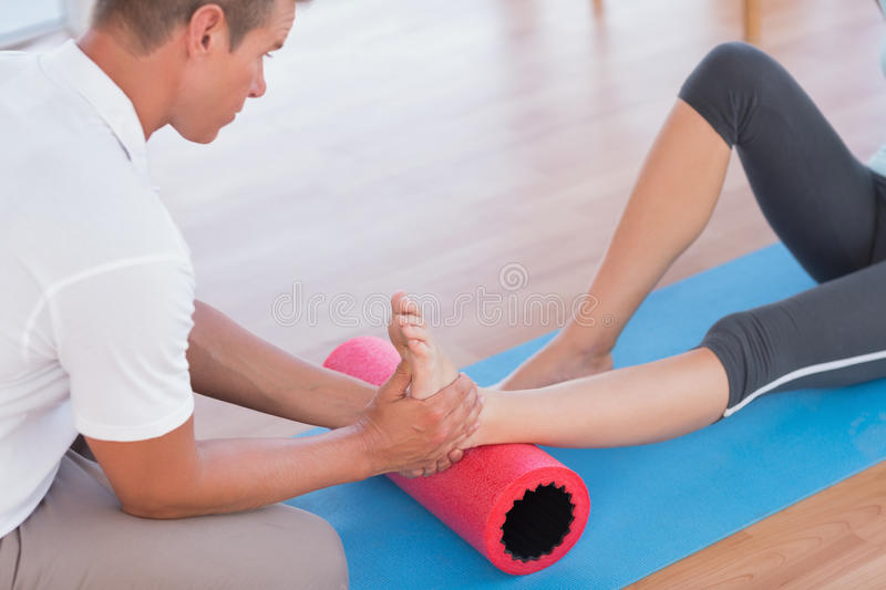 Trainer working with woman on exercise mat royalty free stock images