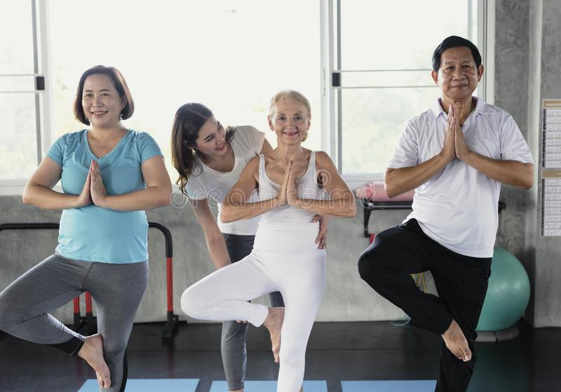 Trainer Young Female Performing yoga teach seniors elderly sports class.  stock photos