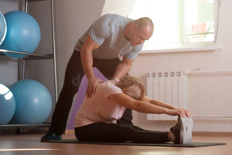 Trainermann hilft älterer Frau, den Körper auszudehnen lizenzfreie stockbilder