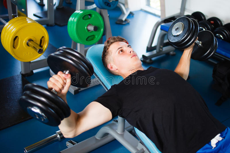 Trainieren mit dumbells an der Gymnastik lizenzfreies stockfoto