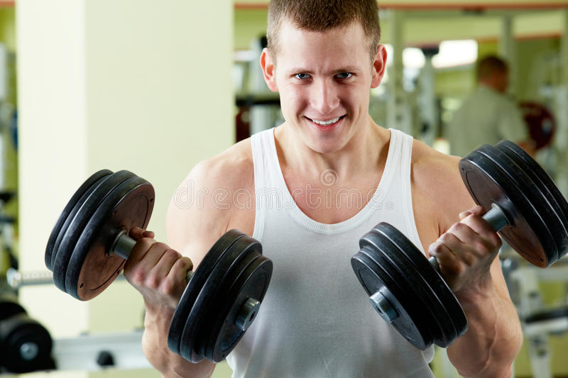 Training. Portrait of sporty man with two dumbbells looking at camera stock image