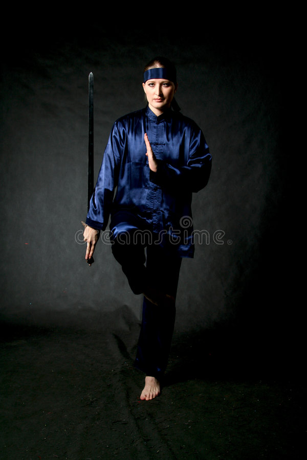 Training. Women in Chinese costume with sword - training stock photo