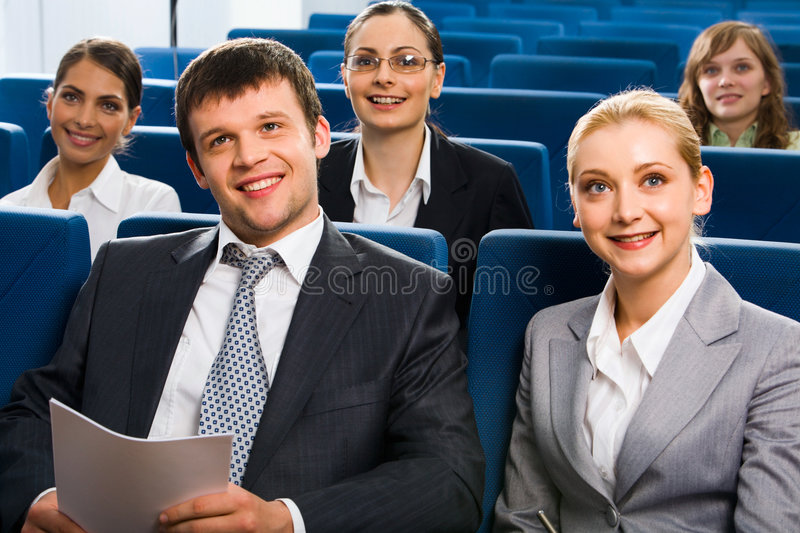 Training. Group of smiling students sitting on the blue chairs in conference hall listening lecture