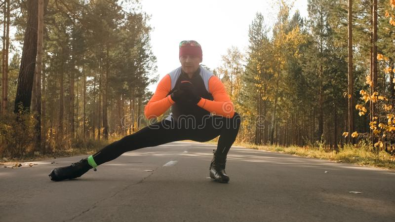 Training an athlete on the roller skaters. Biathlon ride on the roller skis with ski poles, in the helmet. Autumn. Workout. Roller sport. Adult man riding on royalty free stock image